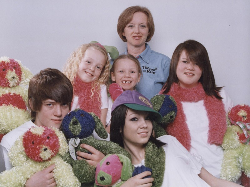 Jill poses with her grandchildren and a stuffed Domino from Through the Rug