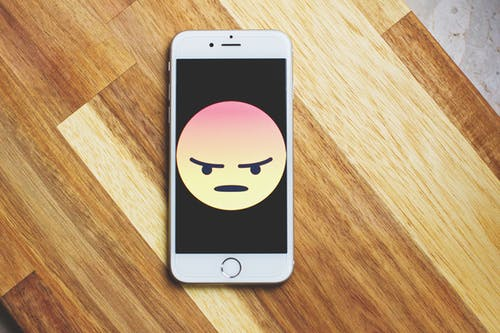 An I phone with an angry face--Using offensive language